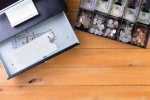 Separate cash drawer beside register on table