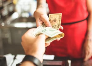A restaurant cashier accepts a cash transaction