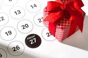 A wrapped gift sits atop a marked calendar