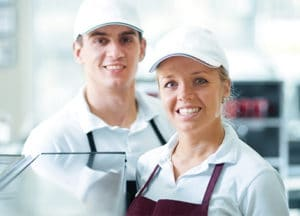 Two restaurant employees smiling while at work