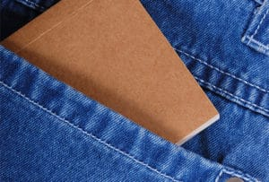 A brown billfold is exposed within the back pocket of a pair of jeans
