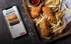 Photo of fast food fries and chicken next to a cell phone with a food delivery website on the screen