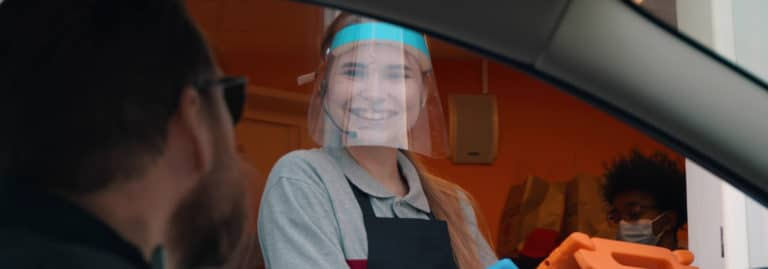 young woman at drive thru with face shield on